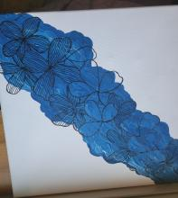 Acrylic painting of blue flowers diagonally on a white canvas